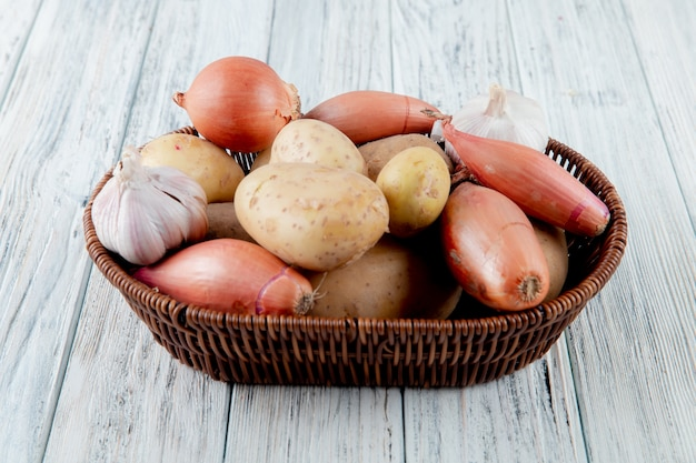 Side view of basket full of vegetables as garlic potato onion on wooden background