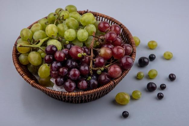 Vista laterale del cesto di uva e acini d'uva su sfondo grigio