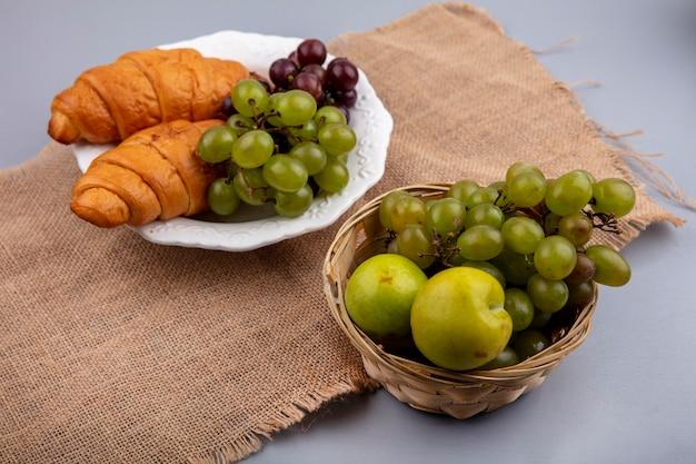 Vista laterale del cesto e piatto di uva con pluots e croissant su tela di sacco su sfondo grigio