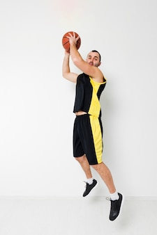 Side view of basketball player dunking mid-air
