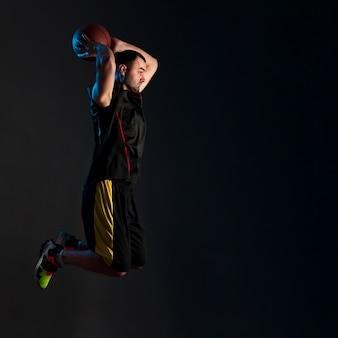 Vista laterale del giocatore di pallacanestro che inzuppa con lo spazio della copia