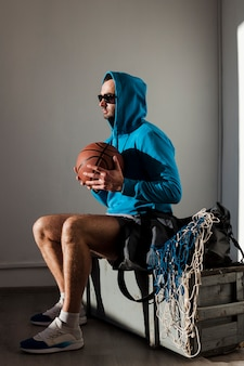 Side view of basketball player posing in hoodie and sunglasses with ball close to chest