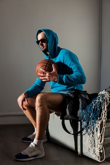 Side view of basketball player posing in hoodie with ball