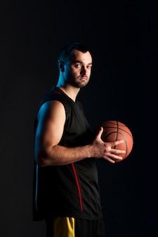 Vista laterale del giocatore di pallacanestro che posa mentre tenendo palla