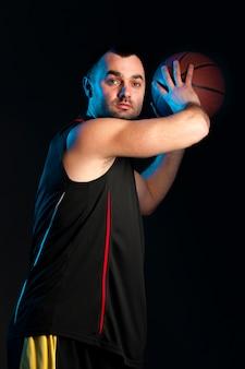 Vista laterale del giocatore di pallacanestro che prepara gettare palla