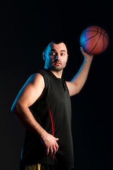 Vista laterale del giocatore di basket con palla in una mano