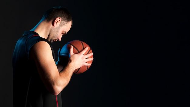 Vista laterale del giocatore di basket con spazio di copia
