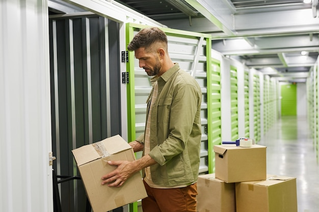 Side view at bearded adult man loading cardboard boxes into self storage unit, copy space