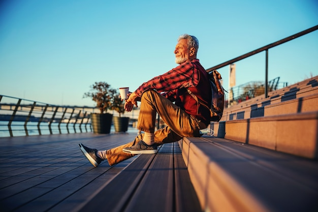 Side view of bearded hipster senior man sitting on the stairs outdoors, drinking coffee and looking at river.