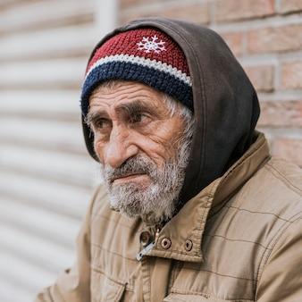 Vista laterale di barbuto senzatetto