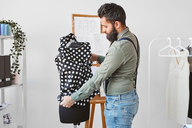 Side view of bearded male fashion designer working with dress form in atelier