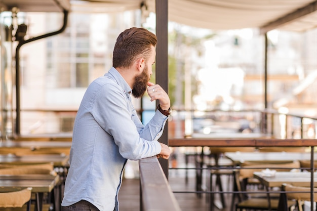 Side view of a bearded man standing in restaurant