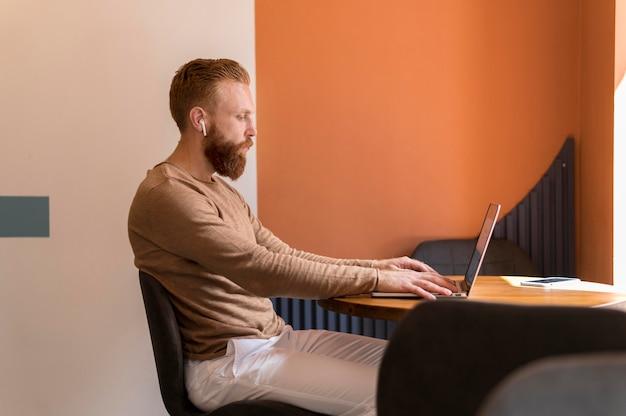 Uomo barbuto di vista laterale che lavora al computer portatile