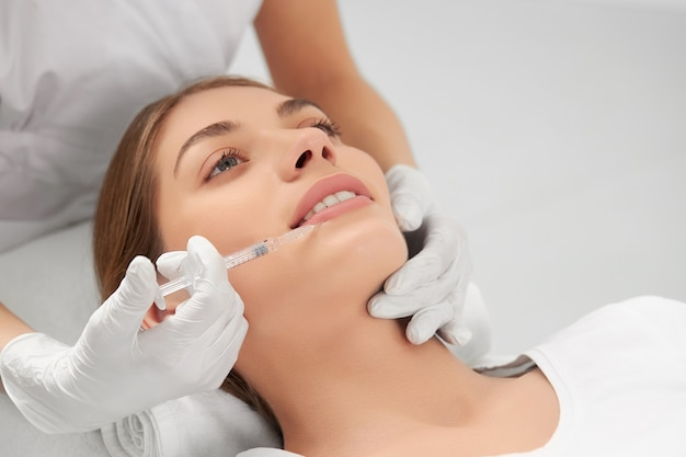 Side view of beautician in white rubber gloves holding syringe and doing injection for lip augmentation
