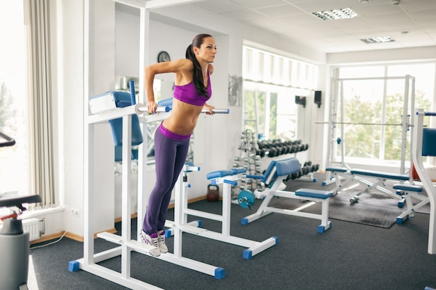 Side view of beautiful athletic lady in sportswear using power tower in modern gym.