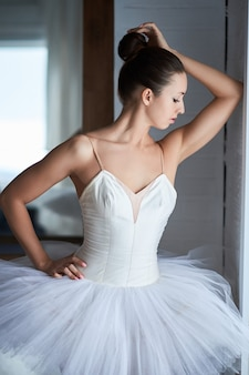 Side view of beautiful ballerina standing and looking through window. copyspace