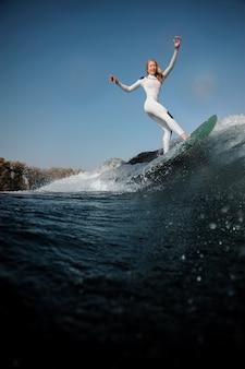 Вид сбоку красивая блондинка в белом купальнике, стоя на вейкборде, поднимая руки