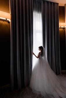 Vista laterale della bella sposa bruna in piedi vicino alla finestra al mattino in una stanza d'albergo buia