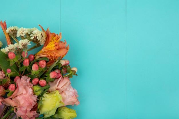 Side view of beautiful colorful flowers with leaves on blue surface with copy space