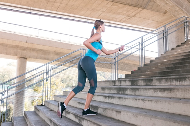 Side view of a beautiful female athlete running on staircase