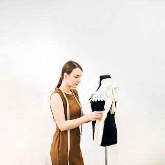 Side view of a beautiful female designer sewing dress
