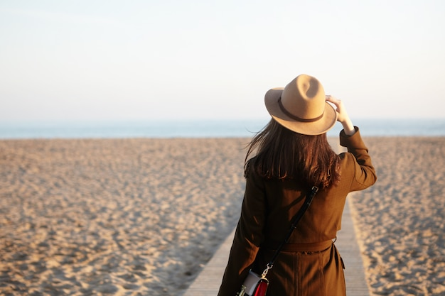 Side view of beautiful female stranger on autumn sand beach. brunette woman looking into distance, noticed ship or dolphin in sea or ocean, adjusting her beige hat with hand, mind full of thoughts