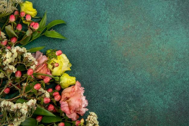 Vista laterale di bei e fiori freschi con le foglie su superficie verde con lo spazio della copia