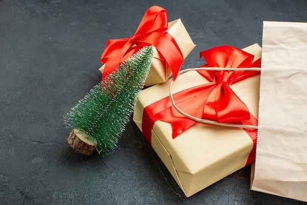 Vista laterale di bellissimi regali con nastro rosso e albero di natale su un tavolo scuro