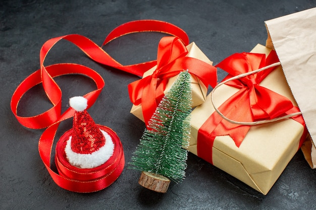 Side view of beautiful gifts with red ribbon and christmas tree santa claus hat on a dark table