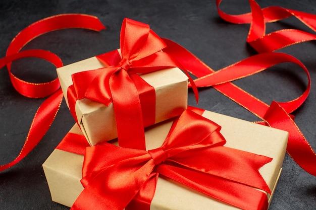 Vista laterale di bellissimi doni con nastro rosso su sfondo scuro