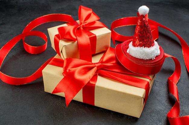 Vista laterale di bellissimi doni con nastro rosso e cappello di babbo natale su sfondo scuro