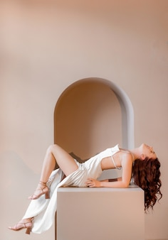 Side view of beautiful red-haired girl lies on a cube in the studio