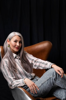 Вид сбоку красивый старший женский портрет позирует на стуле