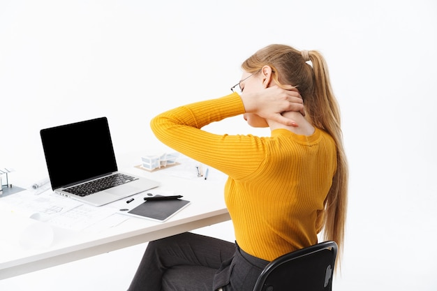 Side view of a beautiful tired young woman graphic designer sitting at the workplace working on blank screen laptop computer and tablet isolated over white wall