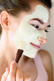 Side view of beautiful woman applying face mask