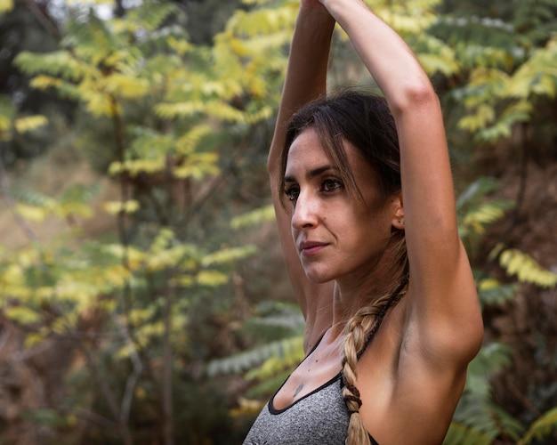 Vista laterale di bella donna che fa yoga in natura
