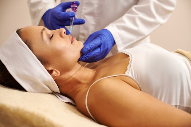 Side view of a beautiful woman getting face lifting treatment at spa salon
