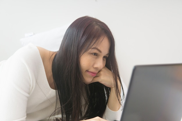 Side view of beautiful woman lying in bed with a laptop