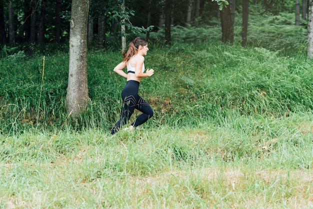 Side view of a beautiful woman running through the green forest with many trees