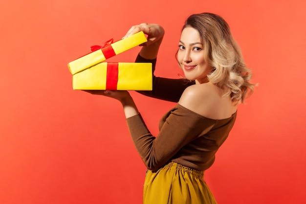 大きな黄色のギフトボックスを開梱し、楽しい笑顔でカメラを見て、プレゼントに満足している側面図の美しい女性。オレンジ色の背景に分離された屋内スタジオショット