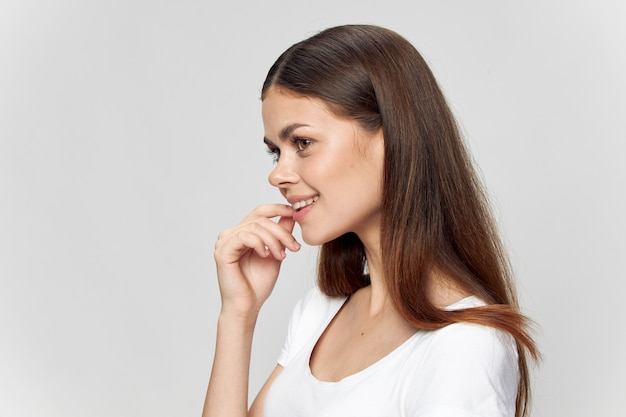 Side view of a beautiful woman in a white t-shirt smiling and looking forward