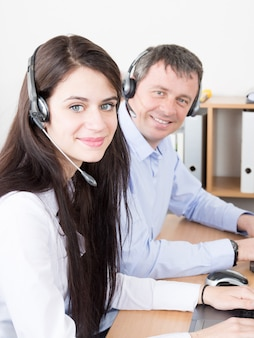 Side view of beautiful young businesswoman and handsome businessman in headsets