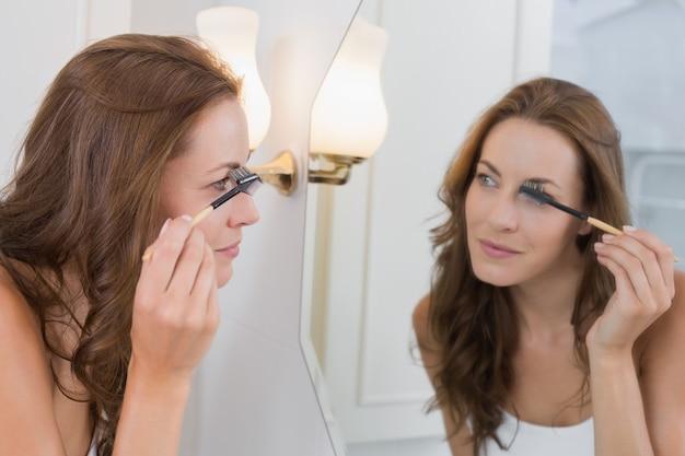 Side view of a beautiful young woman applying mascara