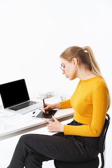 Side view of a beautiful young woman graphic designer sitting at the workplace working on blank screen laptop computer and tablet isolated over white wall