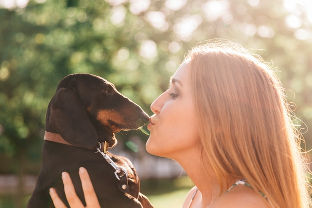 Side view of a beautiful young woman kissing her dog