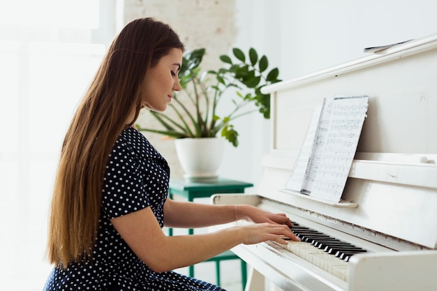 Side view of a beautiful young woman playing the piano