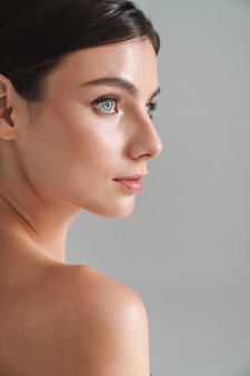 Вид сбоку красоты портрет молодой топлес брюнетки, стоящей изолированной на сером, глядя в сторону