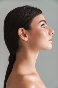 Вид сбоку красоты портрет молодой обнаженной до пояса брюнетки женщины, стоящей изолированной на сером, глядя вверх