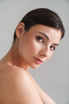 Вид сбоку красоты портрет молодой топлес брюнетки, стоящей изолированной на сером