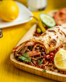 Side view of beef doner wrapped in lavash served with dresh tomatoes and cucumbers on wooden board